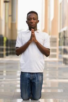 Retrato de joven africano en edificio moderno en la ciudad al aire libre