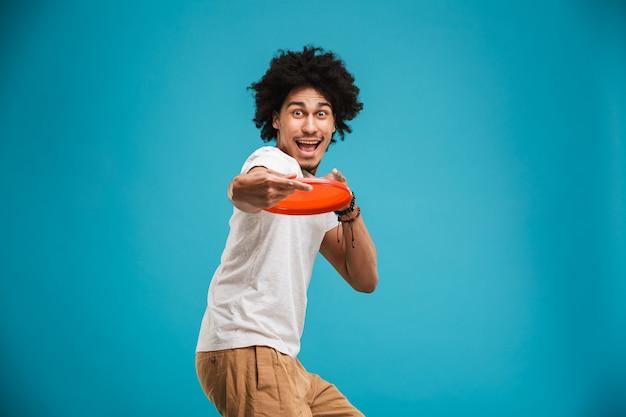 Retrato de un joven africano feliz jugando con frisbee