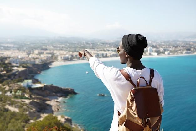 Retrato de un joven africano irreconocible con sombrero negro inconformista de pie en la plataforma de turismo admirando el mar y la hermosa ciudad turística apuntando con el dedo a lugares lejanos que visitará