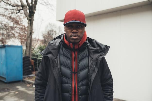Retrato de joven africano de pie en la calle y mirando a cámara