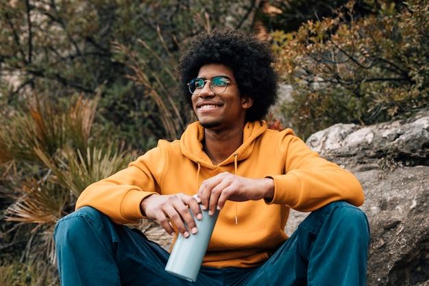 Retrato de un joven africano sonriente sosteniendo la botella de agua en la mano mirando a otro lado