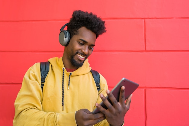 Retrato de joven afro usando su tableta digital con auriculares