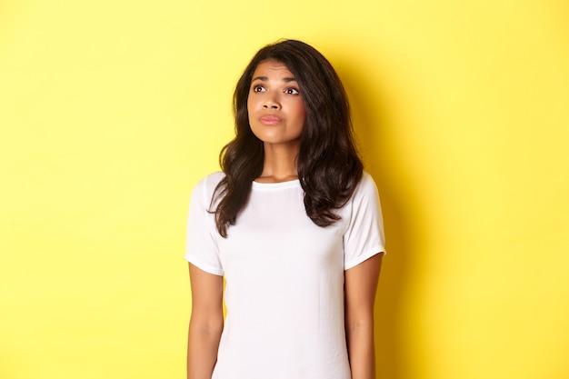 Retrato de una joven afroamericana esperanzada, anhelando algo, mirando la esquina superior izquierda soñadora, de pie sobre fondo amarillo.