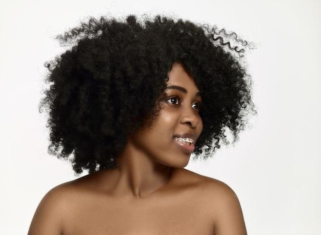 Retrato de joven afroamericana negra sonriente y sorprendida mujer con tirantes en la pared blanca