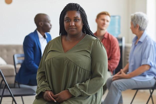 Retrato de joven afroamericana durante la reunión del grupo de apoyo con personas sentadas en círculo en la superficie, espacio de copia