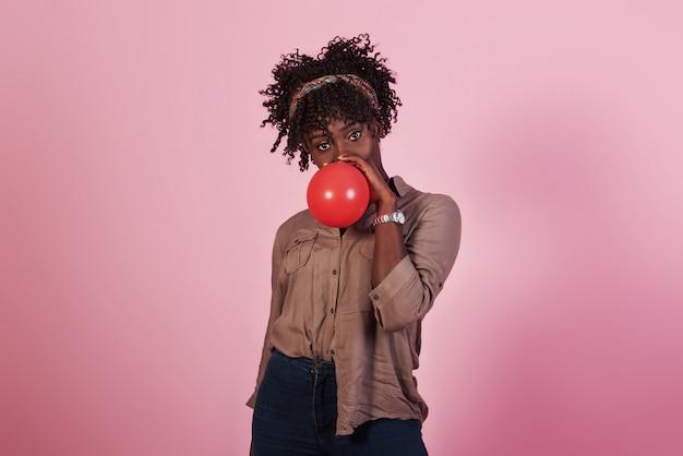 Retrato de joven afroamericana soplando globo rojo ar fondo rosa studio