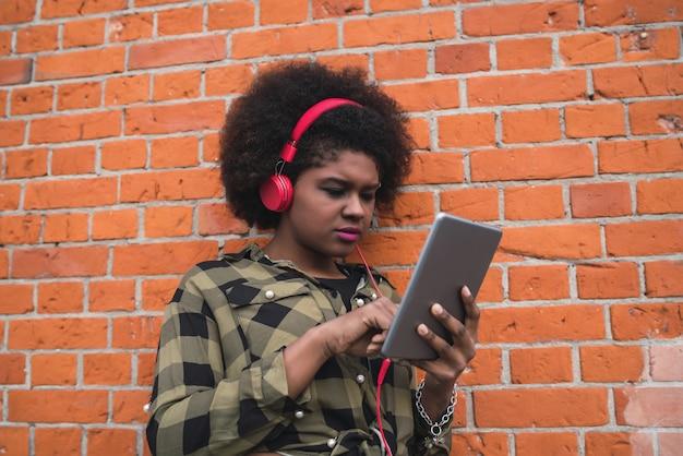 Retrato de joven afroamericana usando su tableta digital con auriculares rojos al aire libre. concepto de tecnología.