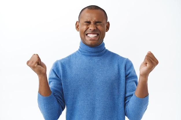 Retrato de joven afroamericano alentado que aumenta la confianza, puñetazos, cierra los ojos y sonríe, motivándose a sí mismo a mantenerse positivo