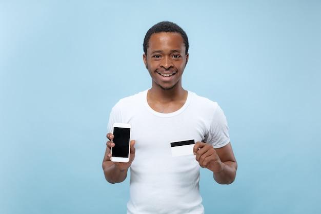 Retrato de joven afroamericano con camisa blanca sosteniendo una tarjeta y un teléfono inteligente.