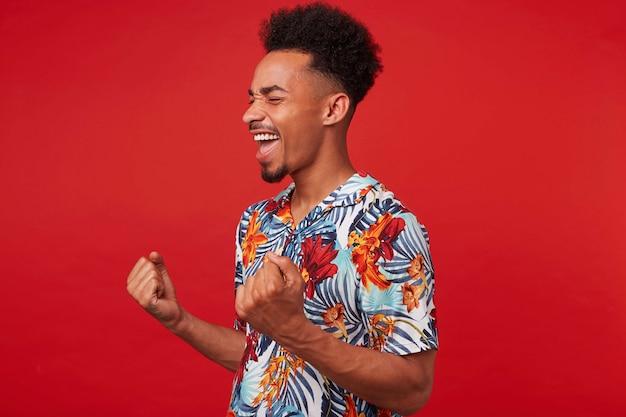 Retrato de joven afroamericano con camisa hawaiana, se ve feliz y alegre, se para sobre fondo rojo y aprieta los puños y se regocija por la victoria.
