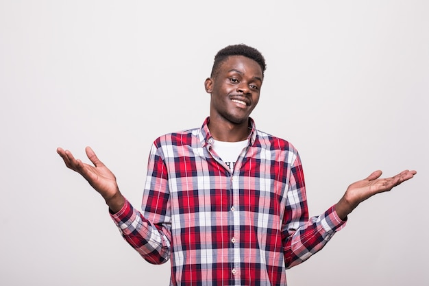 Retrato de joven afroamericano gesticulando no sabe firmar con expresión confusa. aislado
