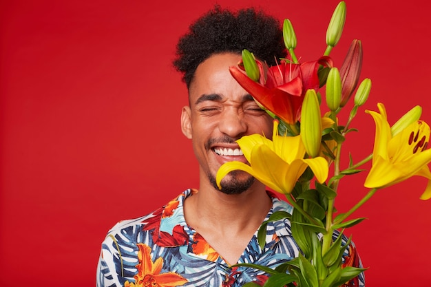 Retrato de joven afroamericano riendo, viste con camisa hawaiana, mira a la cámara con expresión feliz, sostiene flores amarillas y rojas, se encuentra sobre fondo rojo con los ojos cerrados.