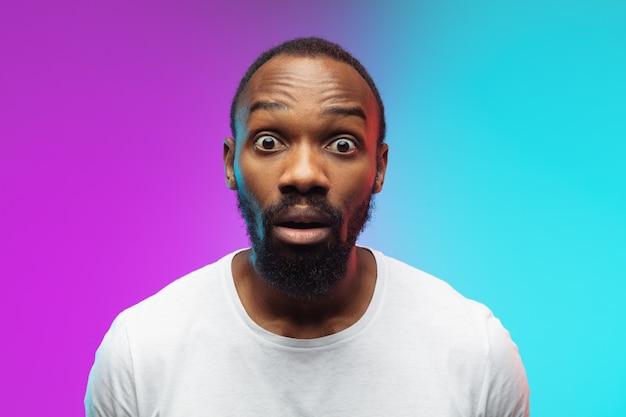 Retrato de joven afroamericano sobre fondo de estudio degradado en neón. hermoso modelo masculino de estilo casual, camisa blanca. concepto de emociones humanas, expresión facial, ventas, publicidad.