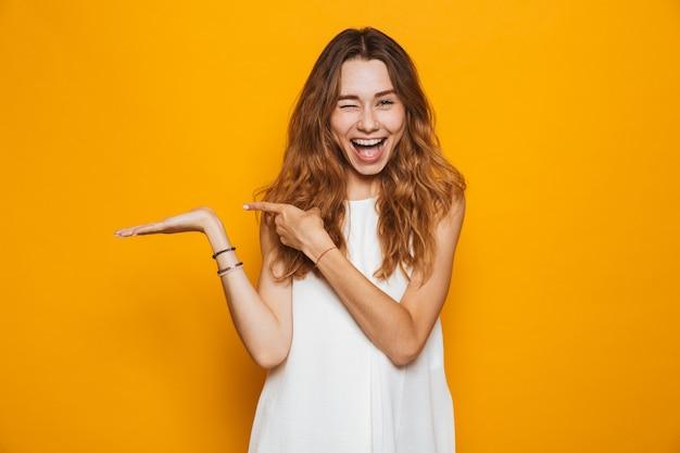Retrato de una joven alegre apuntando hacia afuera