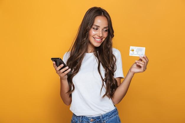 Retrato de una joven alegre con cabello largo morena de pie sobre una pared amarilla, sosteniendo un teléfono móvil, mostrando una tarjeta de crédito de plástico