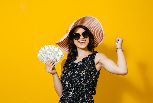 Retrato de una joven alegre con gafas de sol y sombrero con billetes de dinero y celebrando aislado sobre pared amarilla
