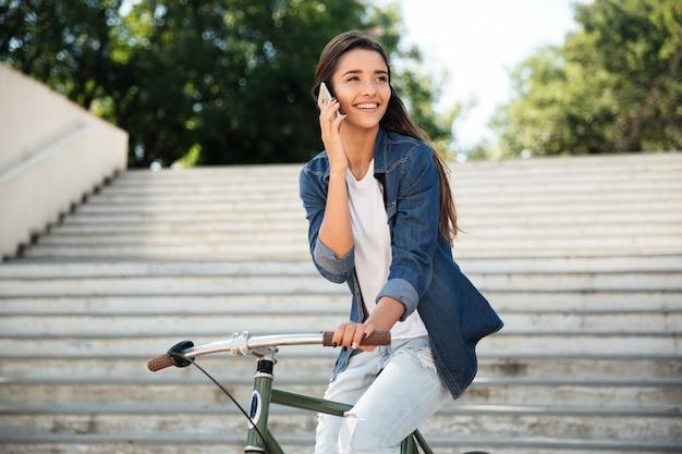 Retrato de una joven alegre, hablando por teléfono móvil