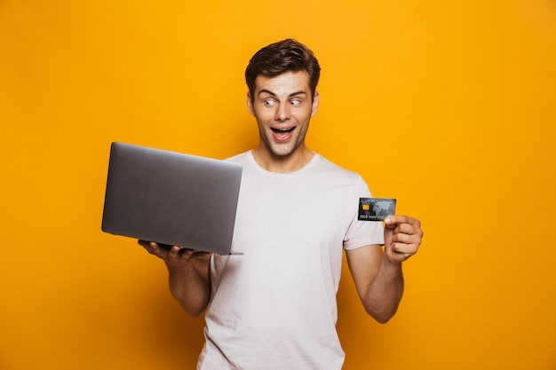 Retrato de un joven alegre con ordenador portátil
