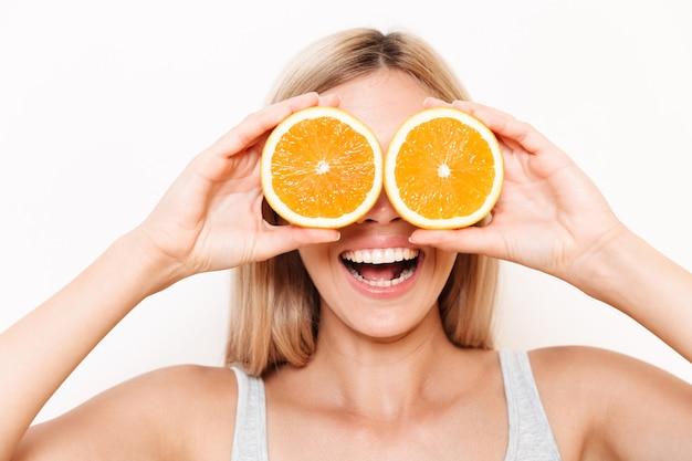Retrato de una joven alegre que cubre sus ojos con fruta naranja