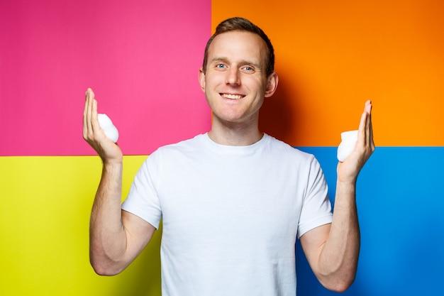 Retrato de un joven alegre sobre un fondo multicolor, vestido con una camiseta blanca, vertió espuma para el cabello en sus manos, crea un peinado de moda