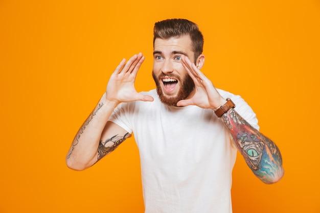 Retrato de un joven alegre vistiendo ropa casual que se encuentran aisladas sobre la pared amarilla, gritando