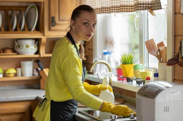Retrato de joven ama de casa hermosa en delantal negro limpieza toallitas para el hogar encimera de cocina con detergente en aerosol