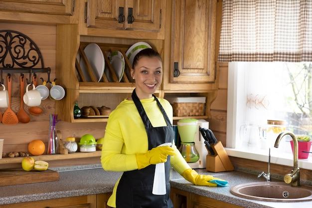 Retrato de joven ama de casa hermosa en delantal negro de pie con spray limpiador de cocina y paño de microfibra