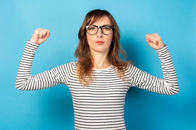 El retrato de una joven amigable con una cara seria en una camiseta casual y gafas hace un gesto de fuerza, confianza en sí mismo en azul. cara emocional gesto culturista