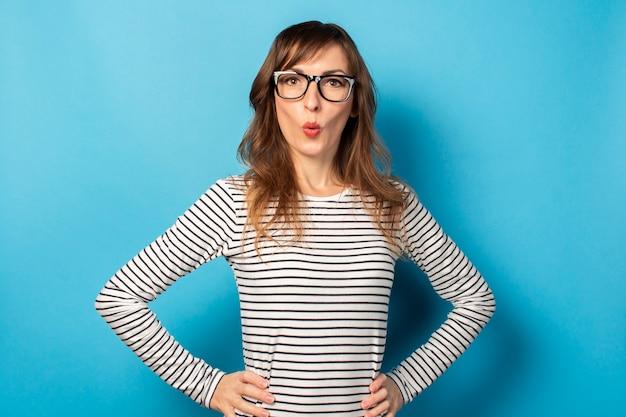 Retrato de una joven amigable con una cara sorprendida en una camiseta casual y gafas de luz