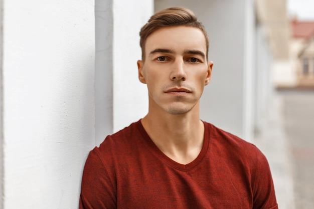 Retrato de un joven apuesto con un corte de pelo en un chaleco cerca de una pared blanca