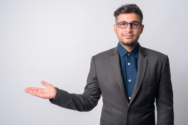 Retrato de joven apuesto empresario iraní en traje con anteojos en blanco