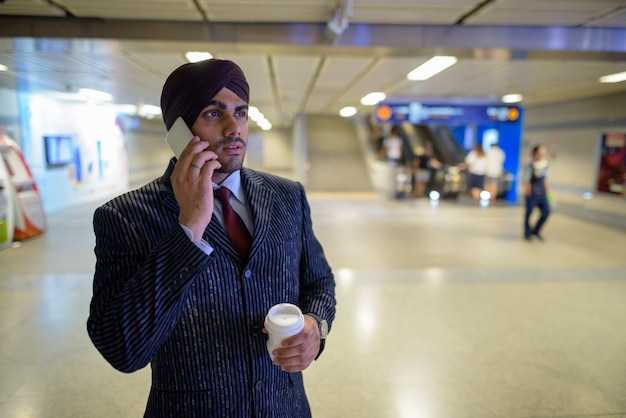 Retrato de joven apuesto empresario sij indio con turbante mientras explora la ciudad de bangkok, tailandia
