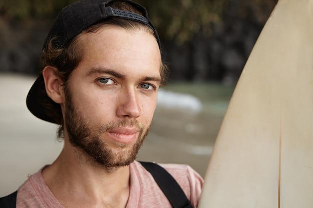 Retrato de joven apuesto ganador del concurso de surf, mirando con sonrisa astuta satisfecha, sosteniendo su tabla de la suerte