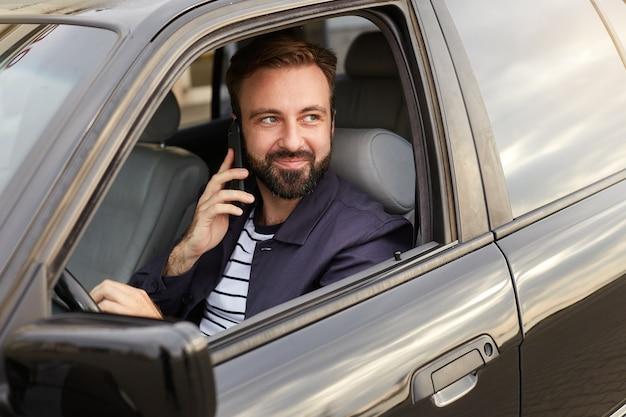 Retrato de joven apuesto hombre barbudo con éxito en una chaqueta azul y camiseta a rayas, se sienta al volante del coche y espera una respuesta en el teléfono de su novia.