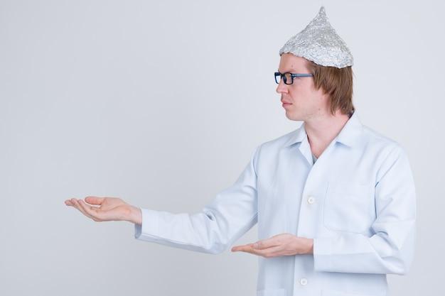 Retrato de joven apuesto médico con sombrero de papel de aluminio como concepto de teoría de la conspiración en blanco