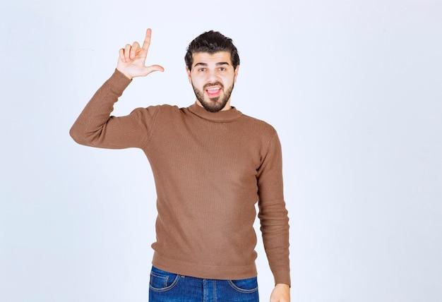 Retrato de un joven apuntando con el dedo hacia arriba en el espacio de la copia aislado sobre fondo blanco. foto de alta calidad Foto gratis