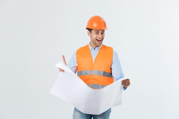Retrato de joven arquitecto feliz con casco y planos de interior.