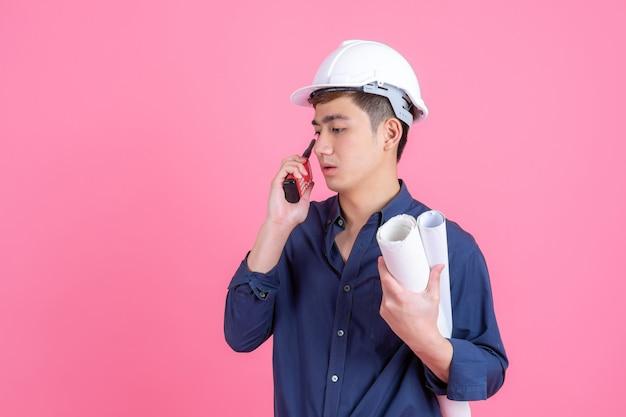 Retrato joven arquitecto hombre con casco blanco y sostenga megáfono en mano