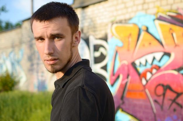 Retrato de joven artista de graffiti en camiseta negra cerca de coloridos graffiti rosa