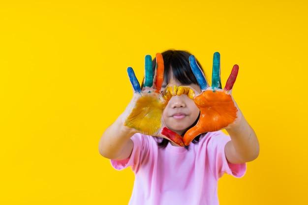 Retrato de joven asiática con arte, niño divertido tailandés muestra el color del agua en la palma en forma de corazón, la creatividad de los niños y el concepto de pintura de amor