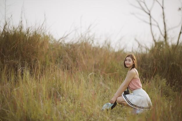 Retrato de joven asiática con cámara en el bosque; fotografía de mujer hermosa en acción. feliz viaje turístico en el parque.