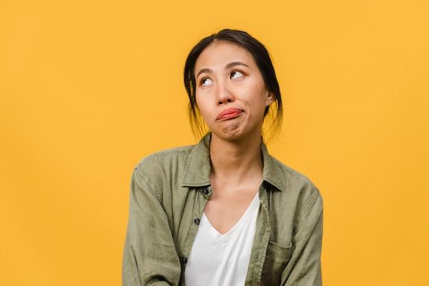 Retrato de joven asiática con expresión negativa, gritando emocionado, llorando emocionalmente enojado en ropa casual aislado en la pared amarilla con espacio de copia en blanco. concepto de expresión facial.