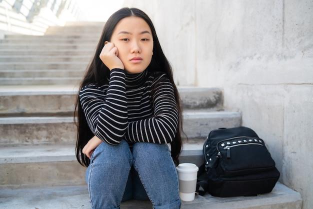 Retrato de joven asiática con expresión pensativa sentado en escaleras de hormigón al aire libre.