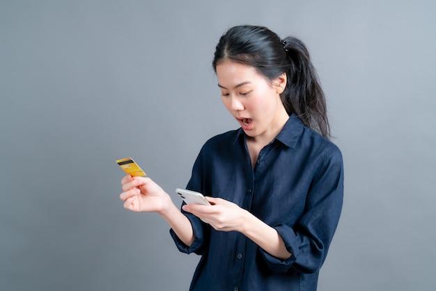 Retrato de una joven asiática feliz mostrando tarjeta de crédito de plástico mientras sostiene el teléfono móvil en la pared gris