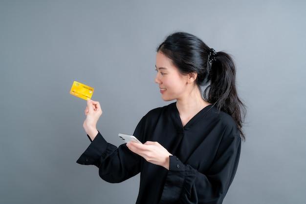 Retrato de una joven asiática feliz mostrando tarjeta de crédito de plástico mientras sostiene el teléfono móvil sobre fondo gris