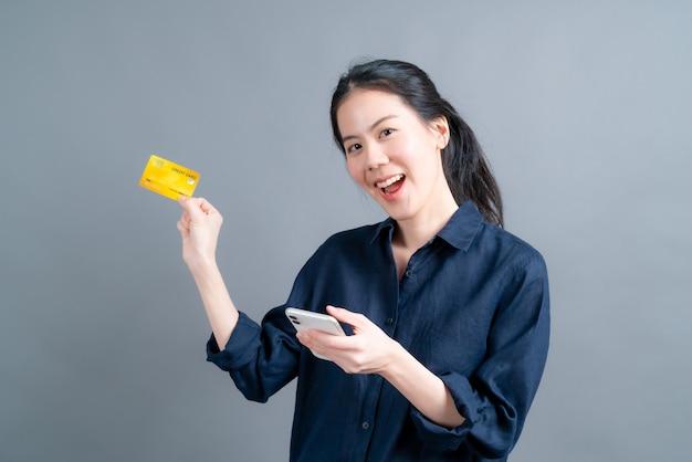 Retrato de una joven asiática feliz mostrando tarjeta de crédito de plástico mientras sostiene el teléfono móvil en la superficie gris