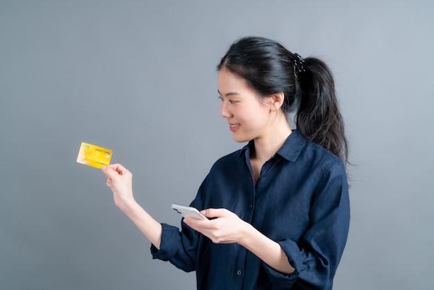 Retrato de una joven asiática feliz mostrando tarjeta de crédito de plástico mientras sostiene el teléfono móvil