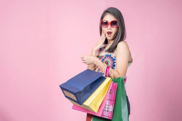 Retrato de joven asiática llevando muchas bolsas de compras