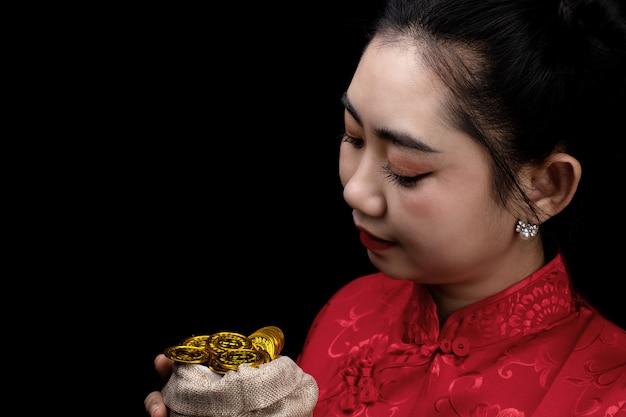 Retrato joven asiática, mujer vestido rojo cheongsam tradicional sosteniendo una moneda de oro en un saco en el fondo negro