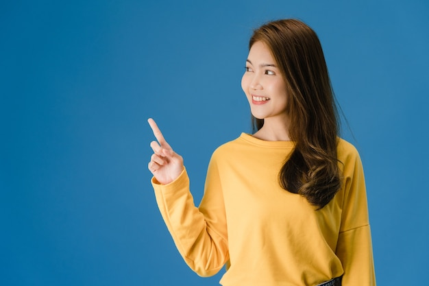 Retrato de joven asiática sonriendo con expresión alegre, muestra algo sorprendente en el espacio en blanco en ropa casual y de pie aislado sobre fondo azul. concepto de expresión facial.